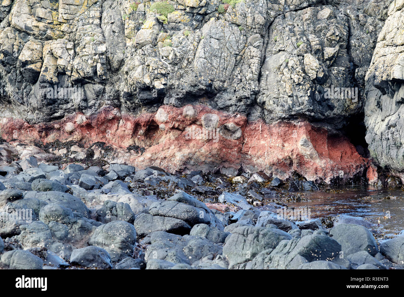 strata of downfaulted basalt rock layers including red band formed of buried ashes Ballintoy county antrim northern ireland - Stock Image