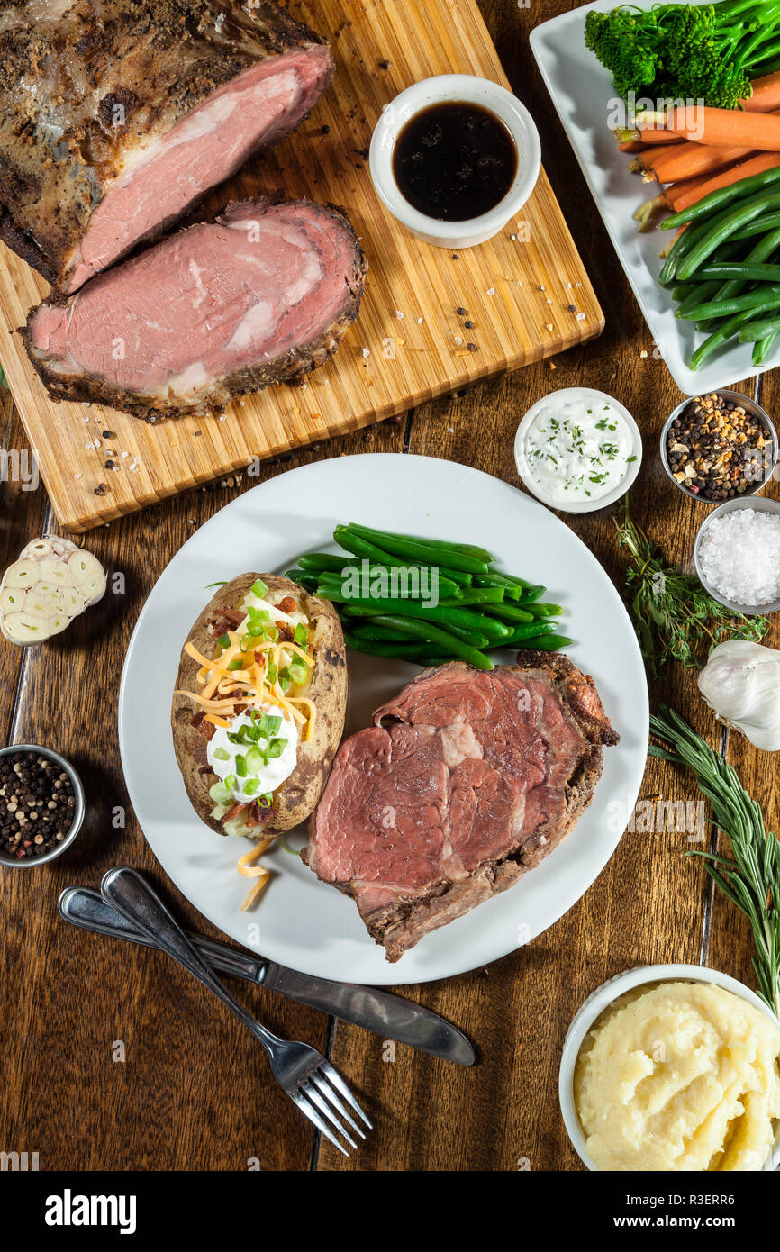 prime rib meal served on a table with ingredients surrounding the main dish Stock Photo