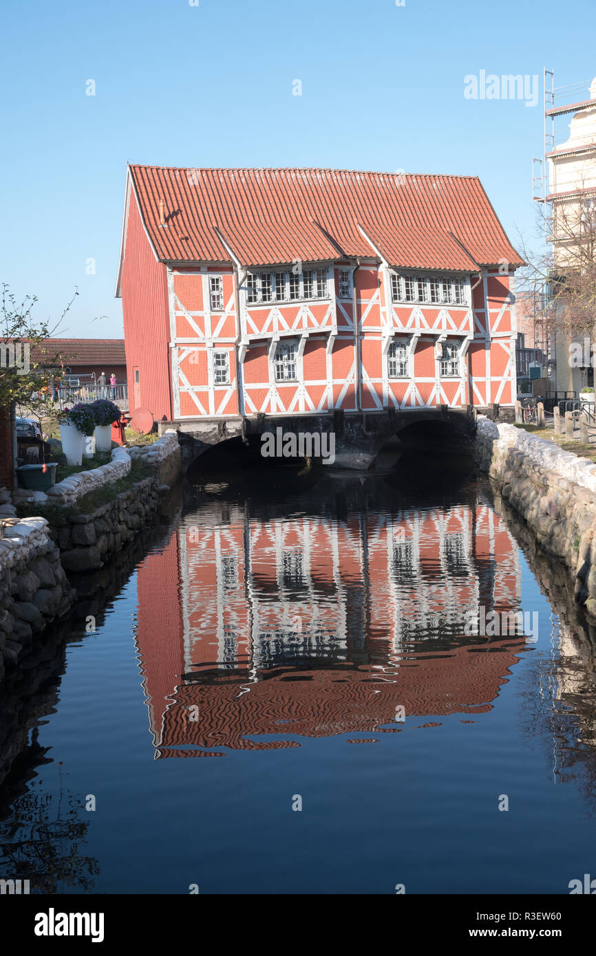 Historical half-timbered house, called Brueckenhaus (bridge house), with reflection in the canal to the harbor of Wismar in Mecklenburg-Vorpommern, No - Stock Image