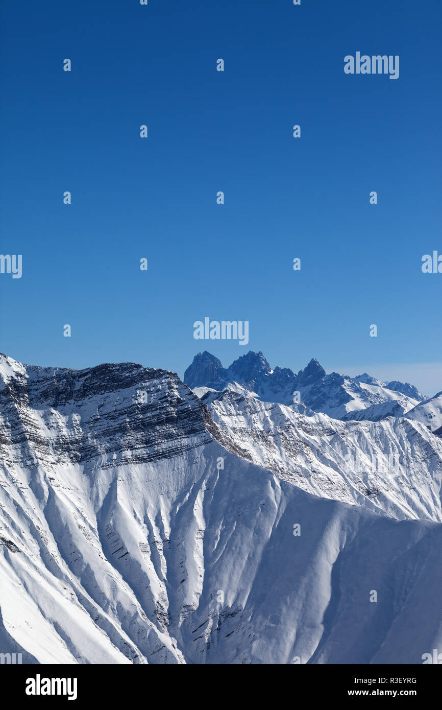 High Rocky Mountains In Snow And Blue Clear Sky At Sun