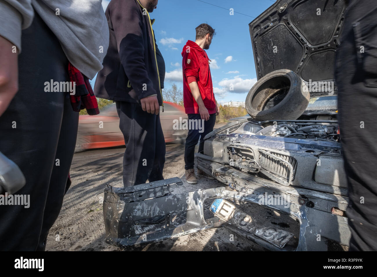 Warsaw / Poland - October 21, 2018: 4 men repairing broken car during amateur drifting event in Ursus, abandoned tractor factory in Warsaw outskirts. - Stock Image