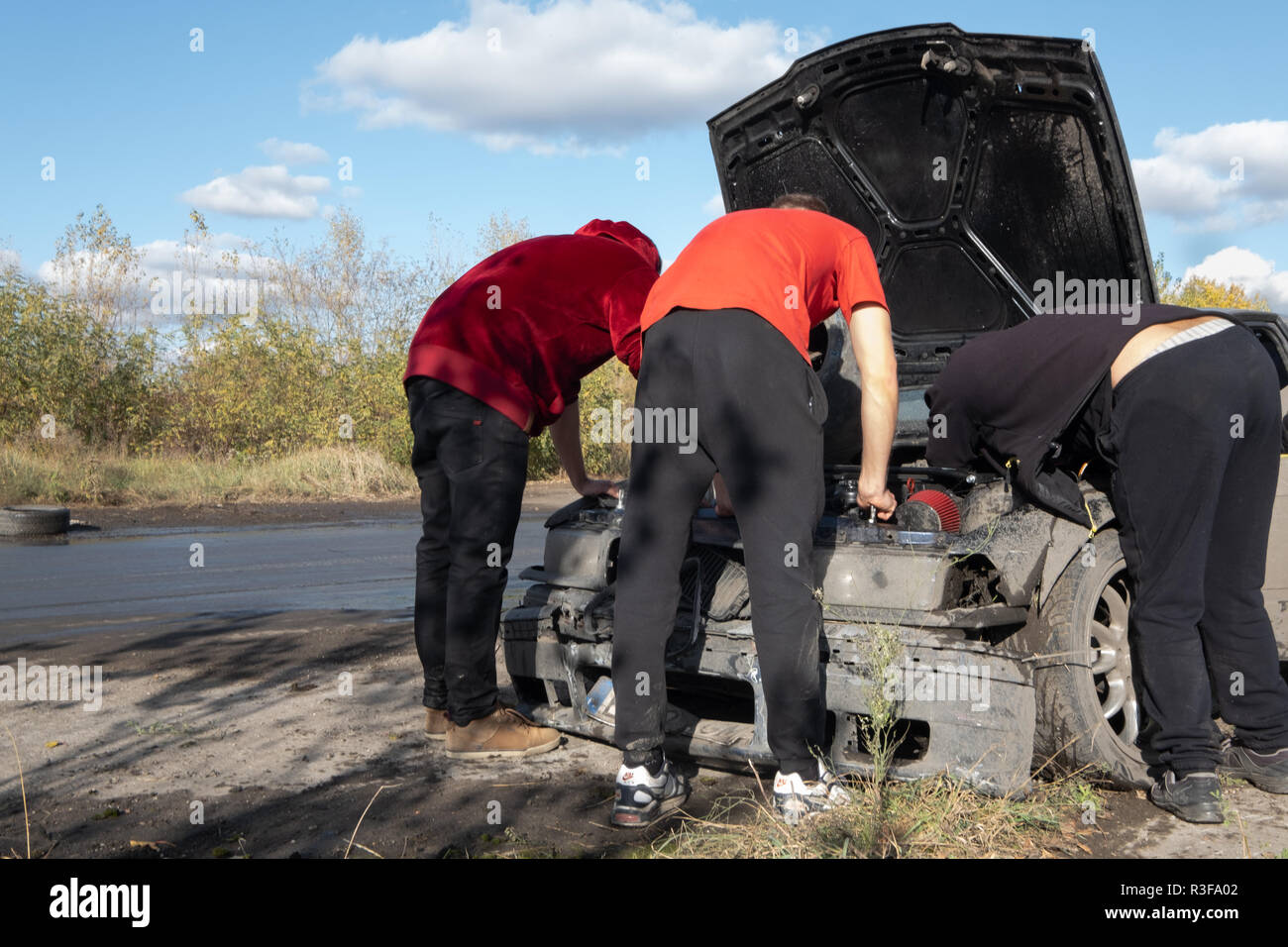 Warsaw / Poland - October 21, 2018: 3 men repairing damaged car during amateur drifting event in Ursus, abandoned tractor factory in Warsaw outskirts. - Stock Image
