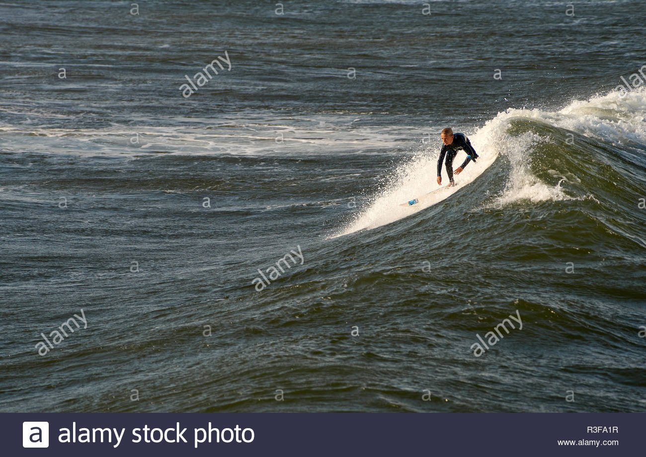 A lone male surfer, riding a wave during a period of moderate swell; surfing at Turners Beach, Yamba, NSW, Australia. - Stock Image