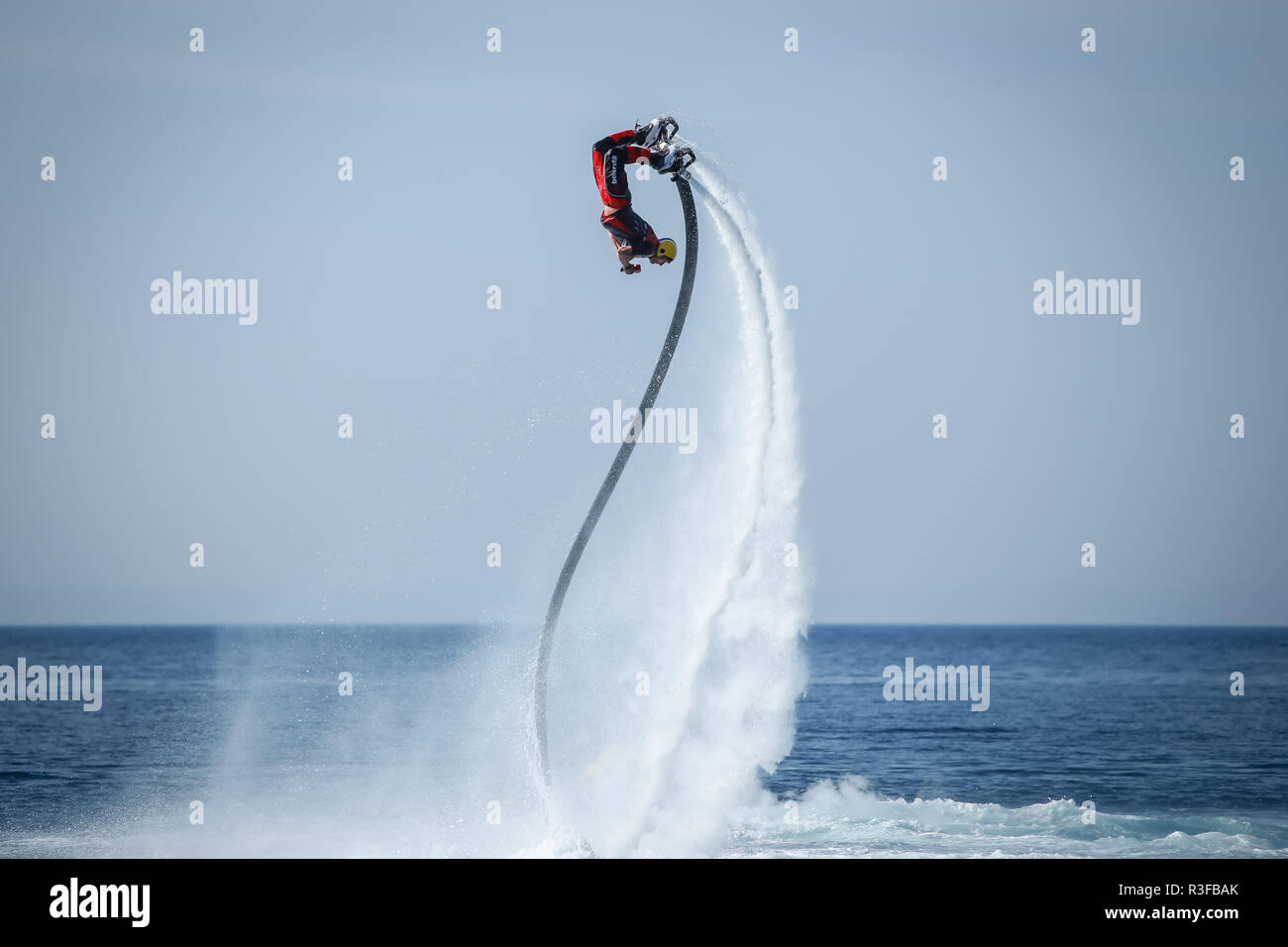 Dugi Rat, Croatia - October 20, 2018: A man is doing acrobatics with flyboard attached to jet ski close to the shore in Dugi Rat, Croatia. Stock Photo