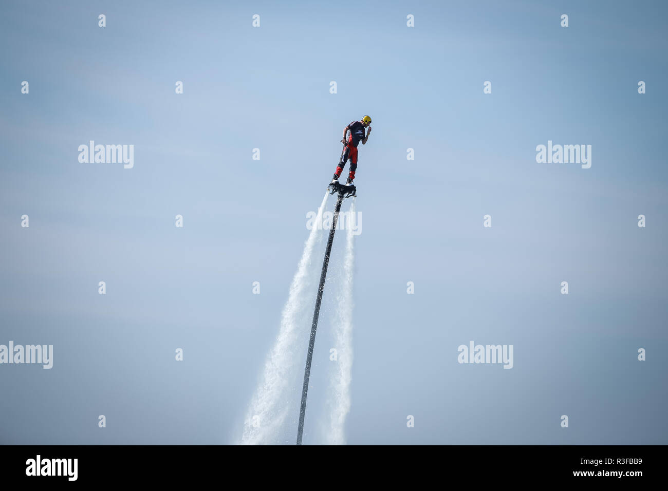 Dugi Rat, Croatia - October 20, 2018: A man is doing acrobatics with flyboard attached to jet ski close to the shore in Dugi Rat, Croatia. - Stock Image