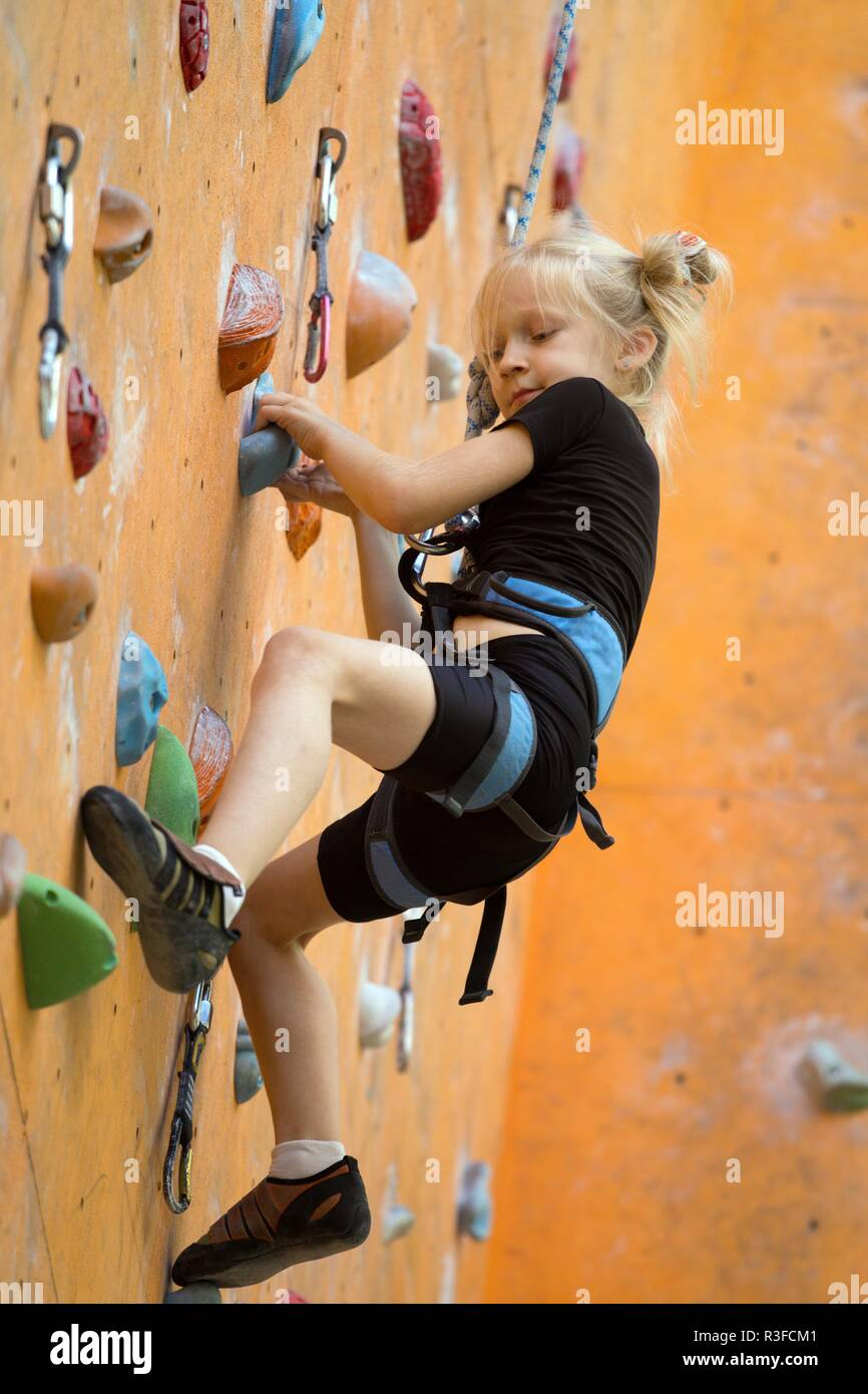 bouldering, little girl climbing up the wall and climber multicolored grips. Leisure activity - Stock Image