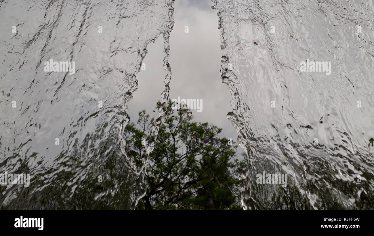 Wide stream of water falling in a semi-translucent park - Stock Image
