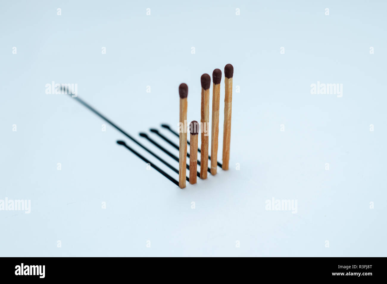 Wooden matches with the wrong shadow on white paper - Stock Image