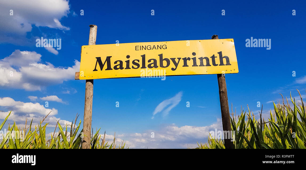 Corn Maze is a maze cut from a corn field. Maize labyrinths are popular with tourists and children. Entrance sign in front of blue sky with lettering  - Stock Image