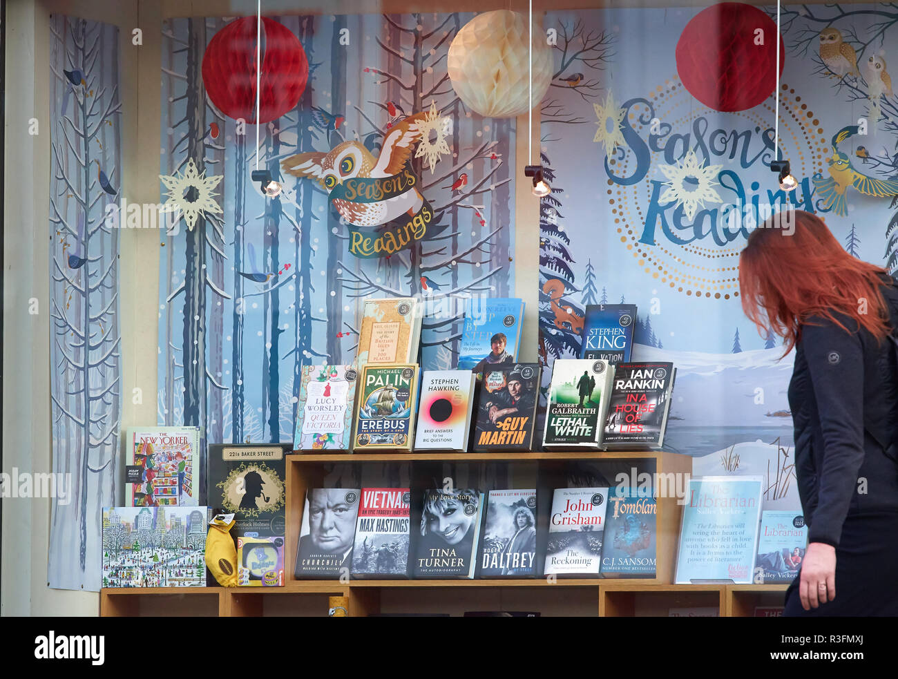 Display of books in a bookshop window with decorations for christmas time and a seasons reading banner. - Stock Image