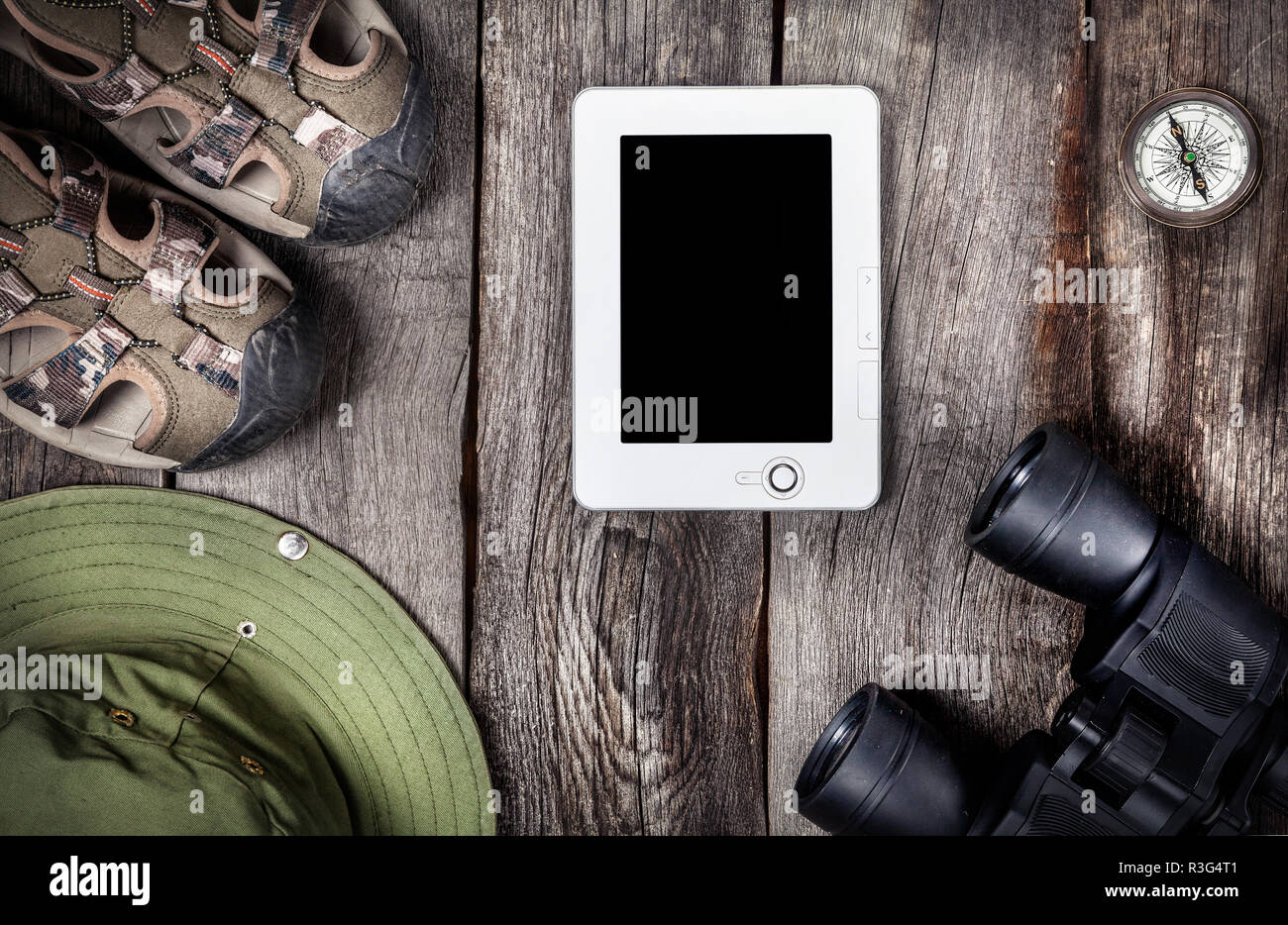 Traveler outfit and tablet on the wooden background - Stock Image