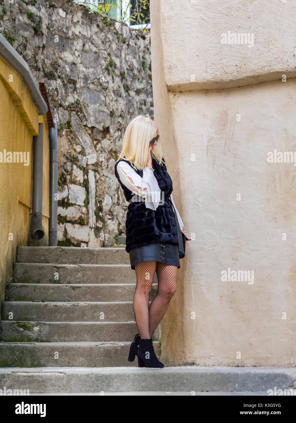Attractive mid-adult senior pretty woman blonde hair outside hidden face and eyes Stock Photo