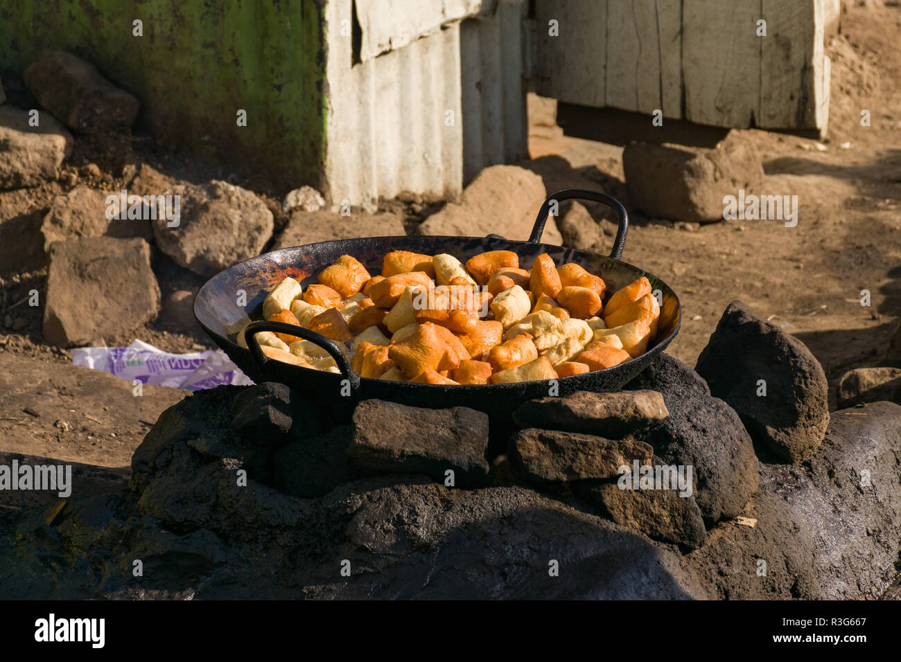 Mandazi A Swahili Fried Bread Snack Also Known As Dabo Or Dahir Being Cooked In A Large Pan On A Stone Fire Pit In The Street Mathare Kenya Stock Photo Alamy