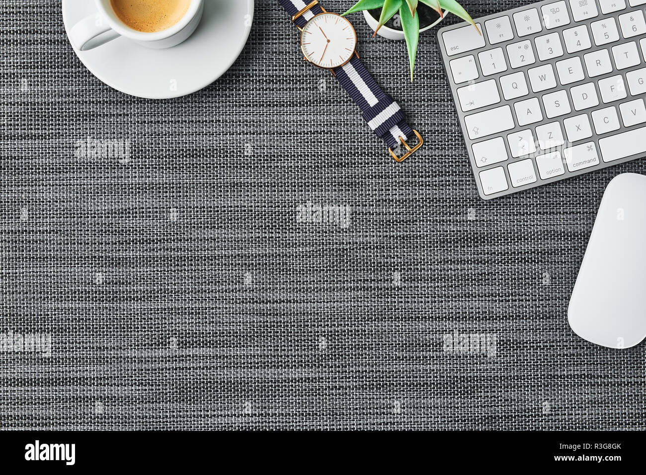 Cozy business composition with white computer keyboard, mouse, coffee cup, women's watch and artificial plant on grey background. Coffee break at the  - Stock Image