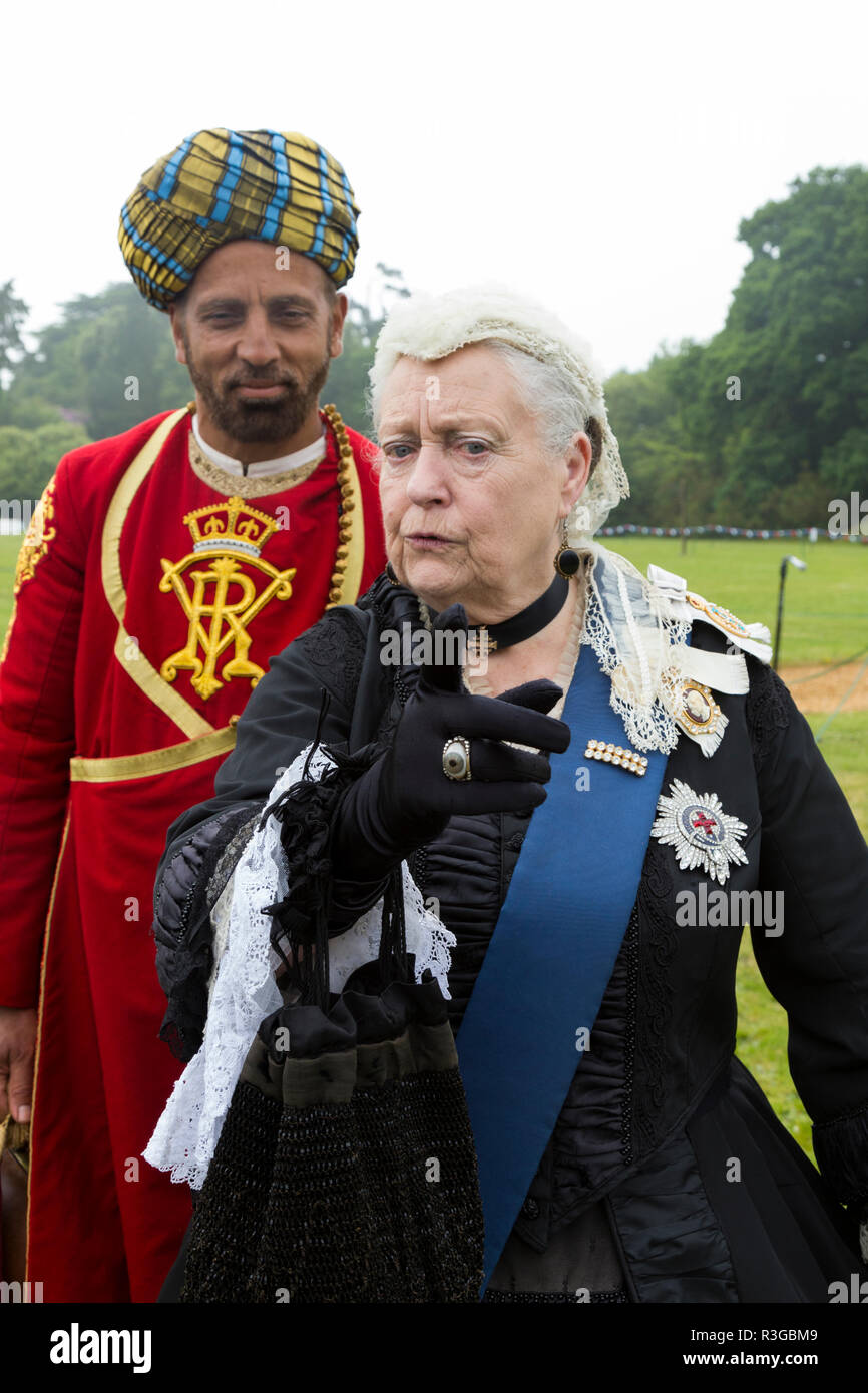 Female actor / actress in the role of Queen Victoria as an old lady towards the end of her reign, accompanied by a Sikh manservant character. Isle of Wight, England. UK. (98) - Stock Image