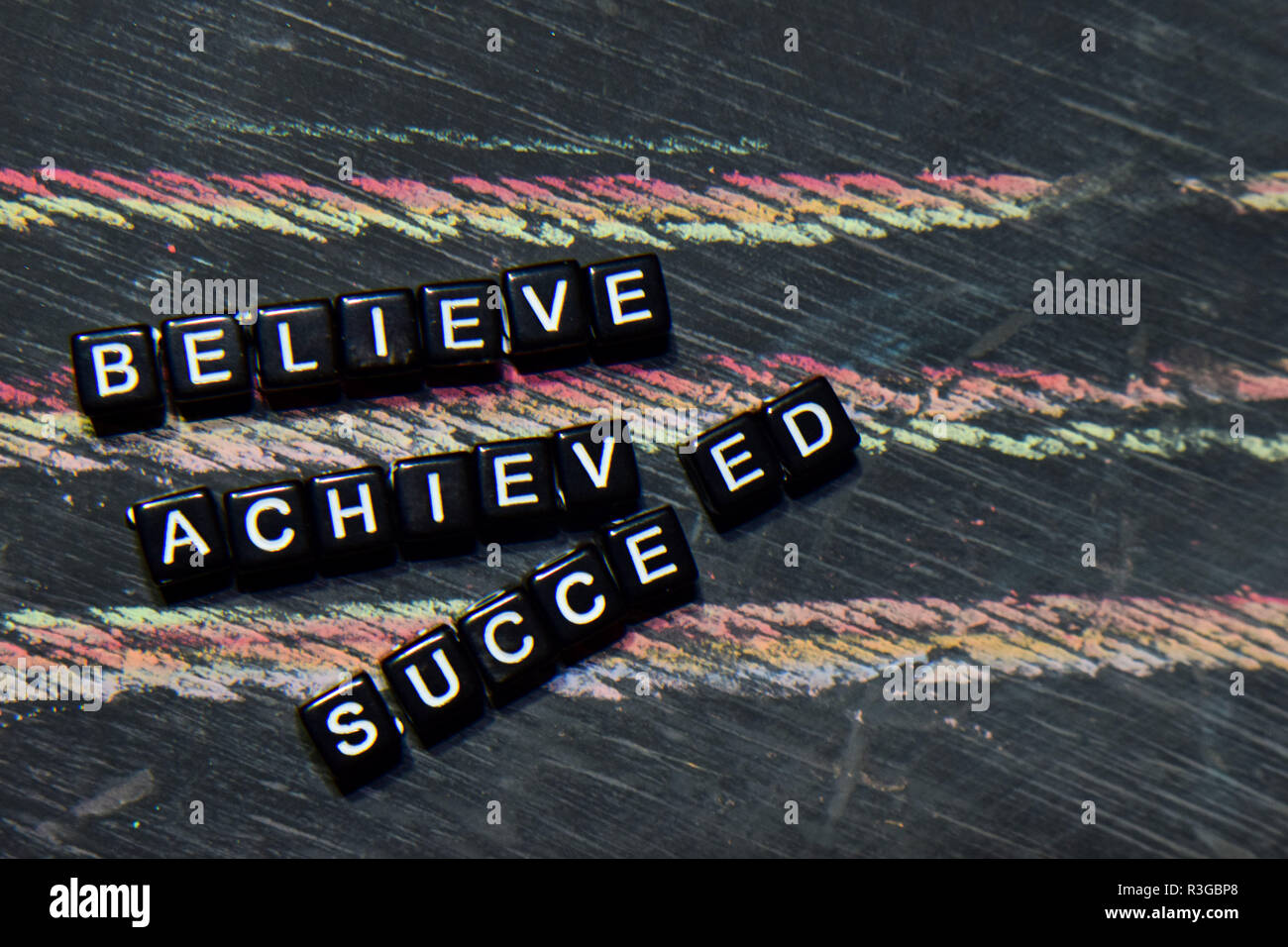 Believe Achieved Succeed on wooden blocks. Cross processed image with blackboard background. Inspiration, education and motivation concepts Stock Photo