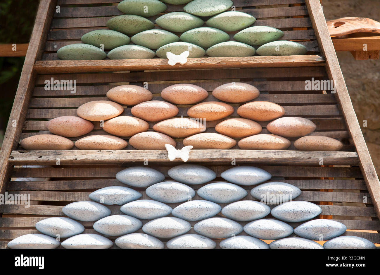 different coloured oval bars of soap stacked nicely in a wooden frame - Stock Image