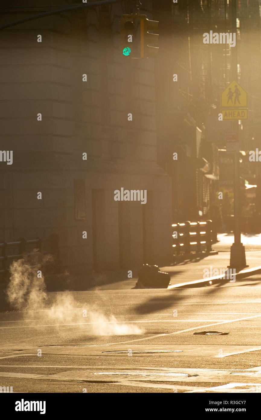 Beautiful sunrise in the streets of Manhattan with a manhole that expels steam, New York, United States. - Stock Image