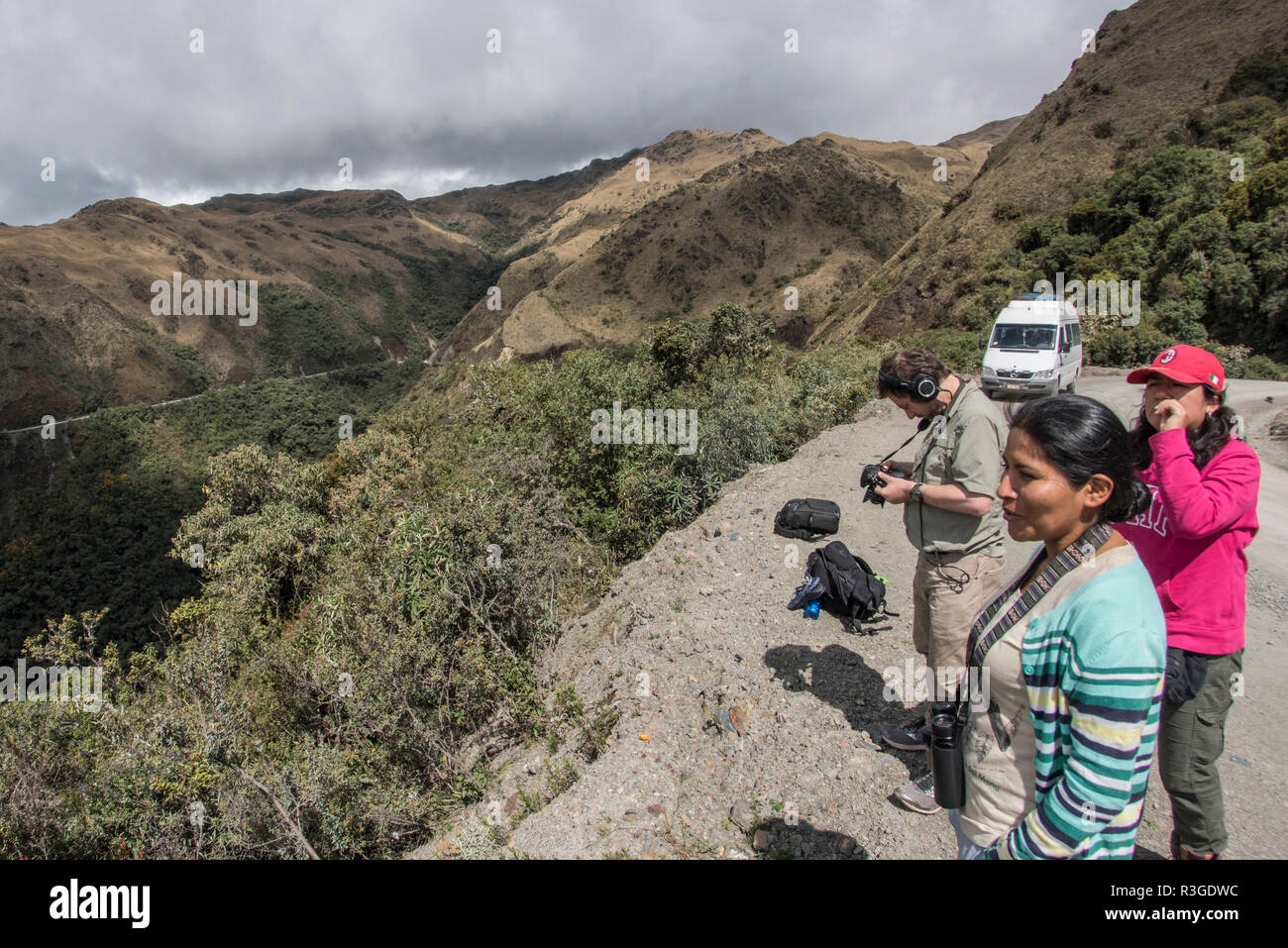 Members of an ecotour stop to look out at a vista along the Manu road in Peru. The road leads through the high Andes mountains. - Stock Image