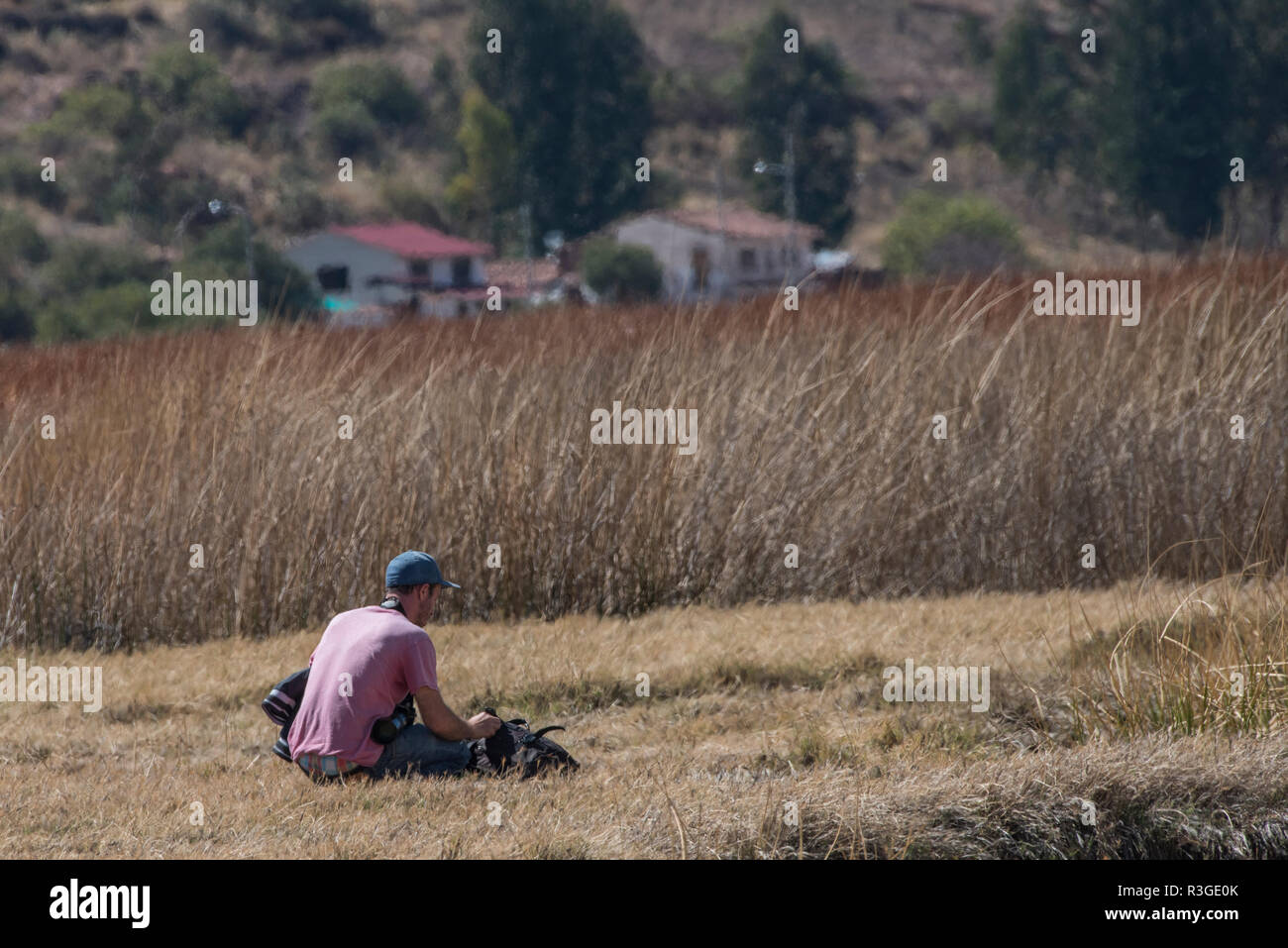 A tourist sits alone in a field in Huarcapay, Peru. - Stock Image
