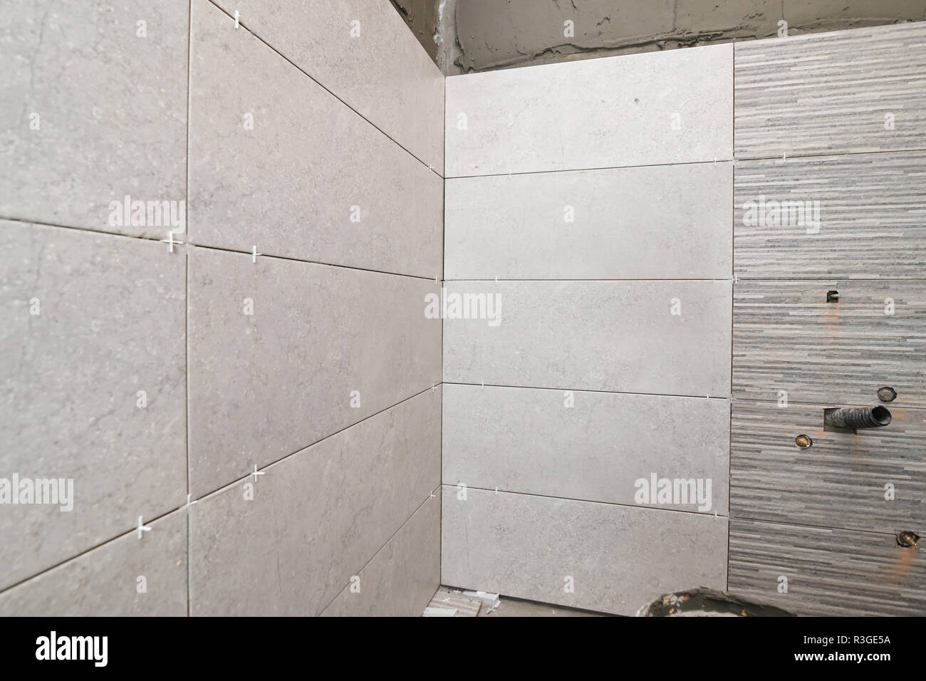Repair the bathroom. Renovation at home unfinished ceramic tiles with spacers - Stock Image