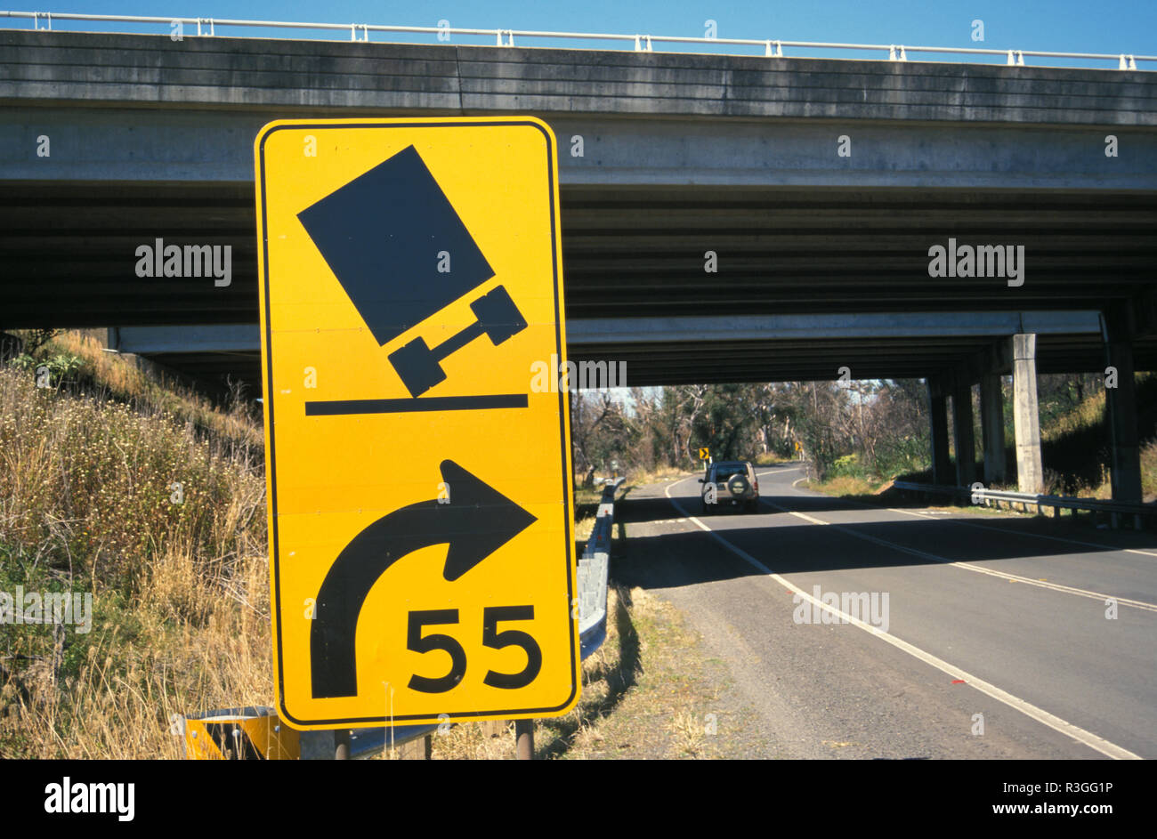 A ROAD SIGN WARNS DRIVERS TO REDUCE SPEED AS A BEND IN THE ROAD APPROACHES (ILLUSTRATED BY TRUCK TIPPING OVER) NEW SOUTH WALES, AUSTRALIA - Stock Image