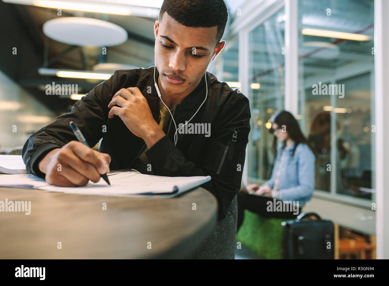 Young man making notes on book. Male student preparing for exams at university library. - Stock Image