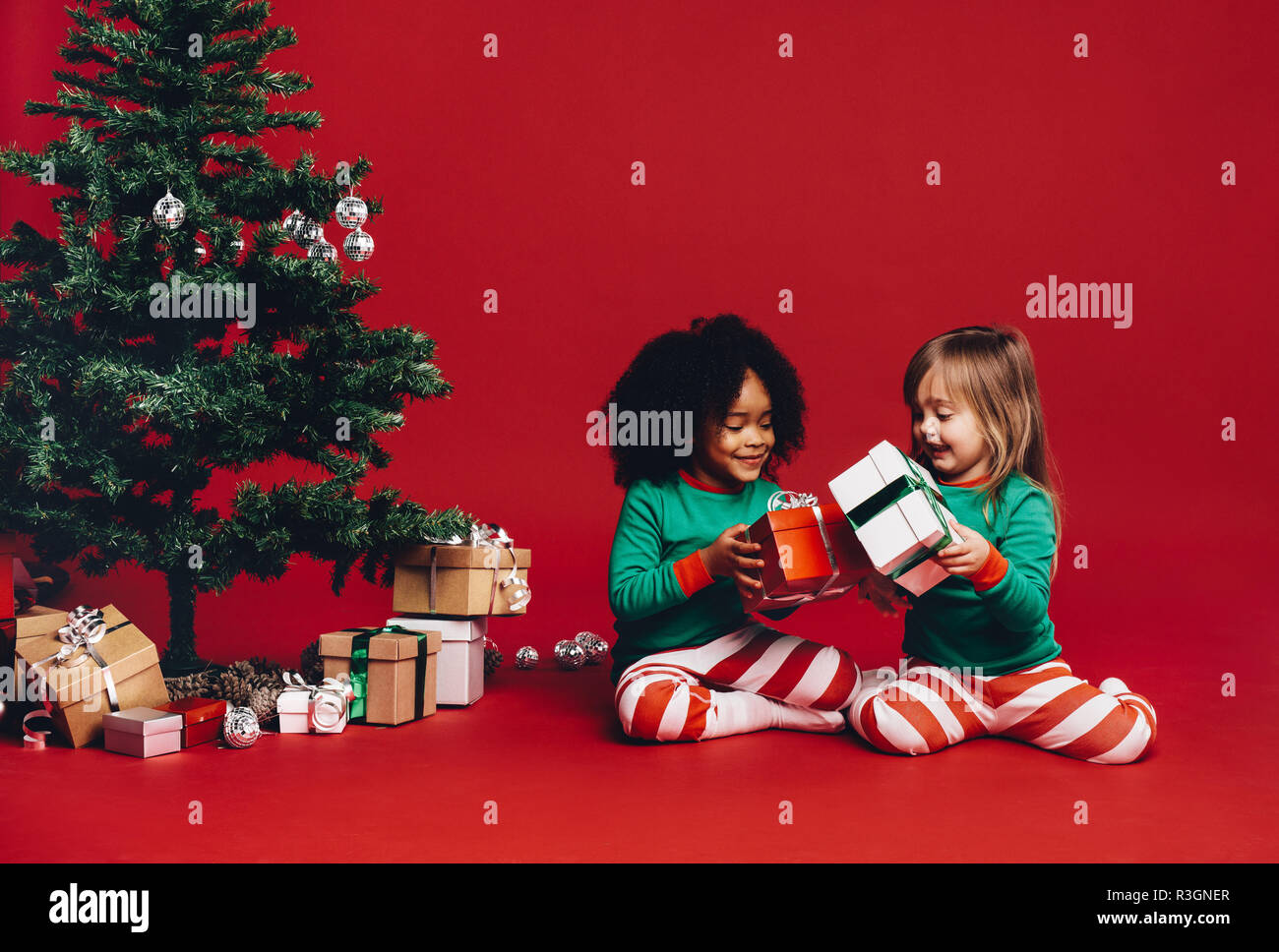 Little Girls Sitting Beside A Christmas Tree Playing With Their Gift Boxes Kids Exchanging Christmas Gifts With A Decorated Christmas Tree And Gift B Stock Photo Alamy