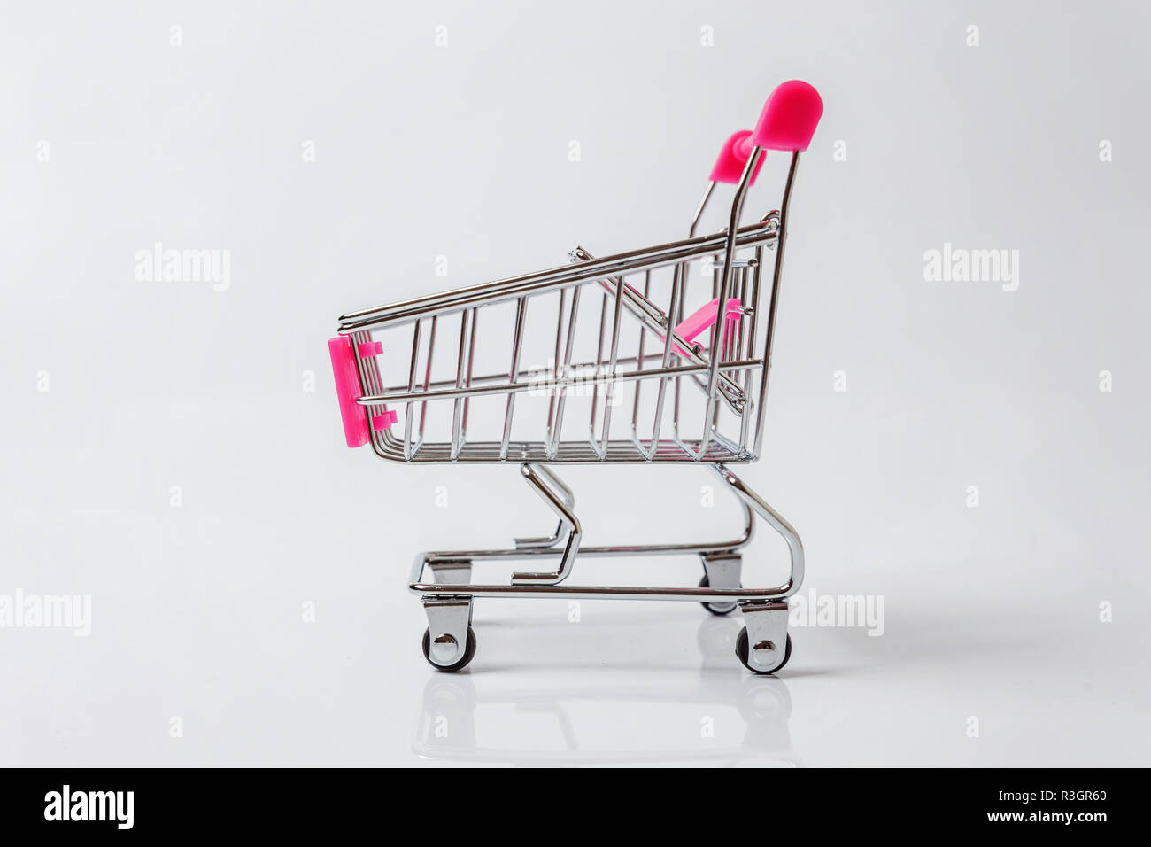 Small supermarket grocery push cart for shopping toy with wheels isolated on white background. Sale buy mall market shop consumer concept. Copy space Stock Photo