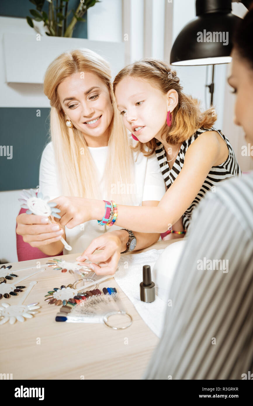 Daughter wearing pink earrings helping her mother in choosing nail color Stock Photo