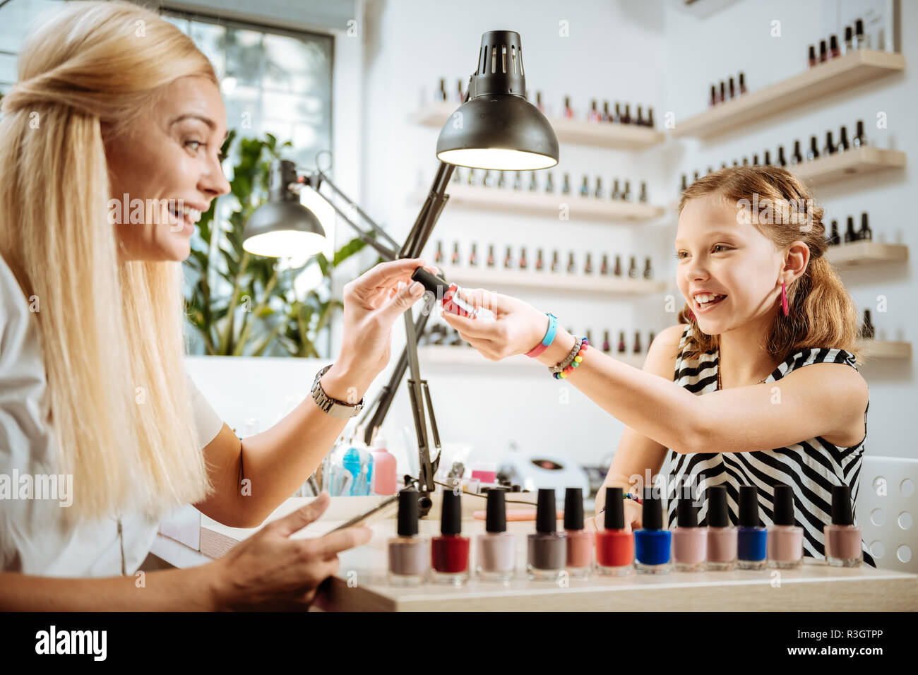Helpful daughter recommending color of nail polish her mother - Stock Image
