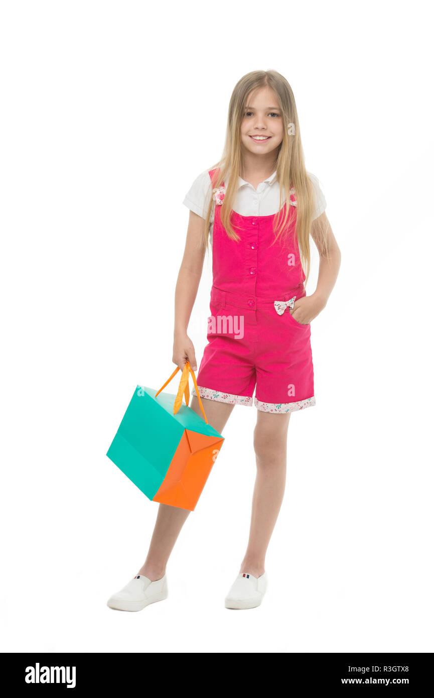 Kids designer clothing summer sale. Girl cute teenager carries shopping bag. Kid bought clothing summer sale. Sale benefits. Seasonal sale concept. Gi - Stock Image