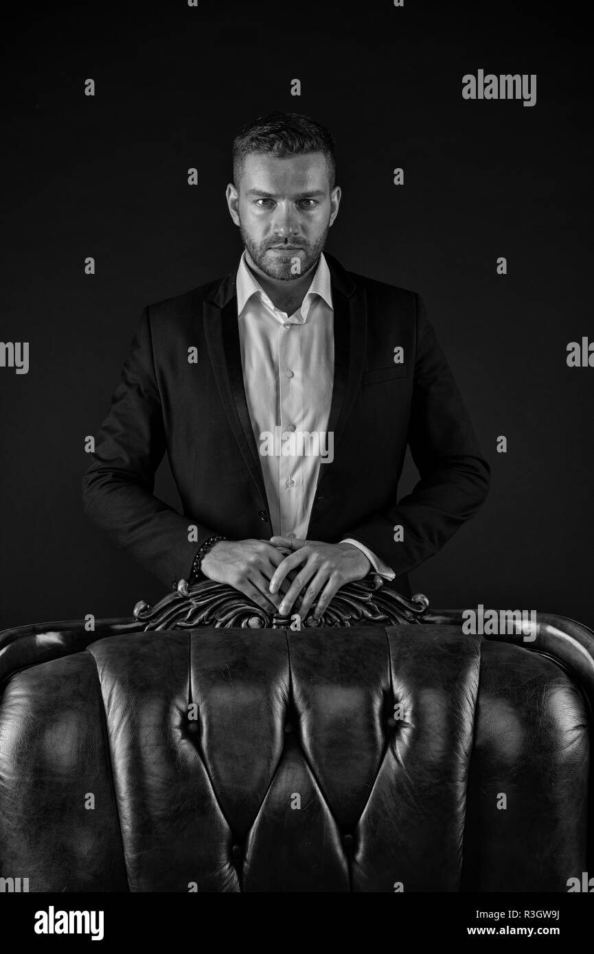 Man in smart suit over dark background. Aristocrat in luxurious interior. Bearded man standing behind leather sofa. Businessman in his mansion, money  - Stock Image