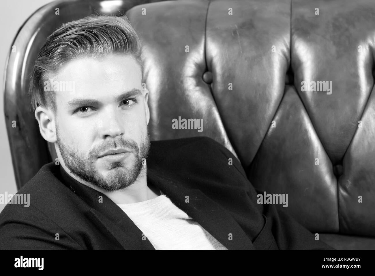 Macho sit in brown leather armchair. Man with unshaven face, blond hair, haircut beauty. Barber salon, barbershop. Beauty, grooming fashion. Confident - Stock Image