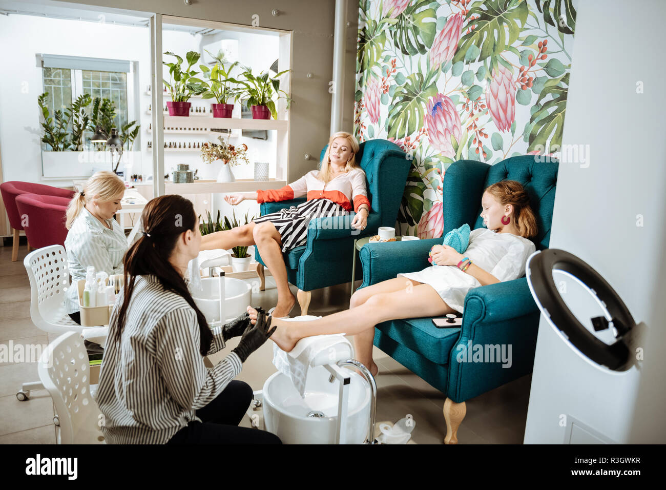 Mother and daughter sitting on comfy armchairs having pedicure - Stock Image