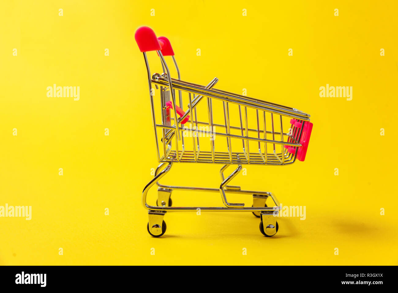 Small supermarket grocery push cart for shopping toy with wheels isolated on yellow colourful trendy modern fashion background. Sale buy mall market s Stock Photo