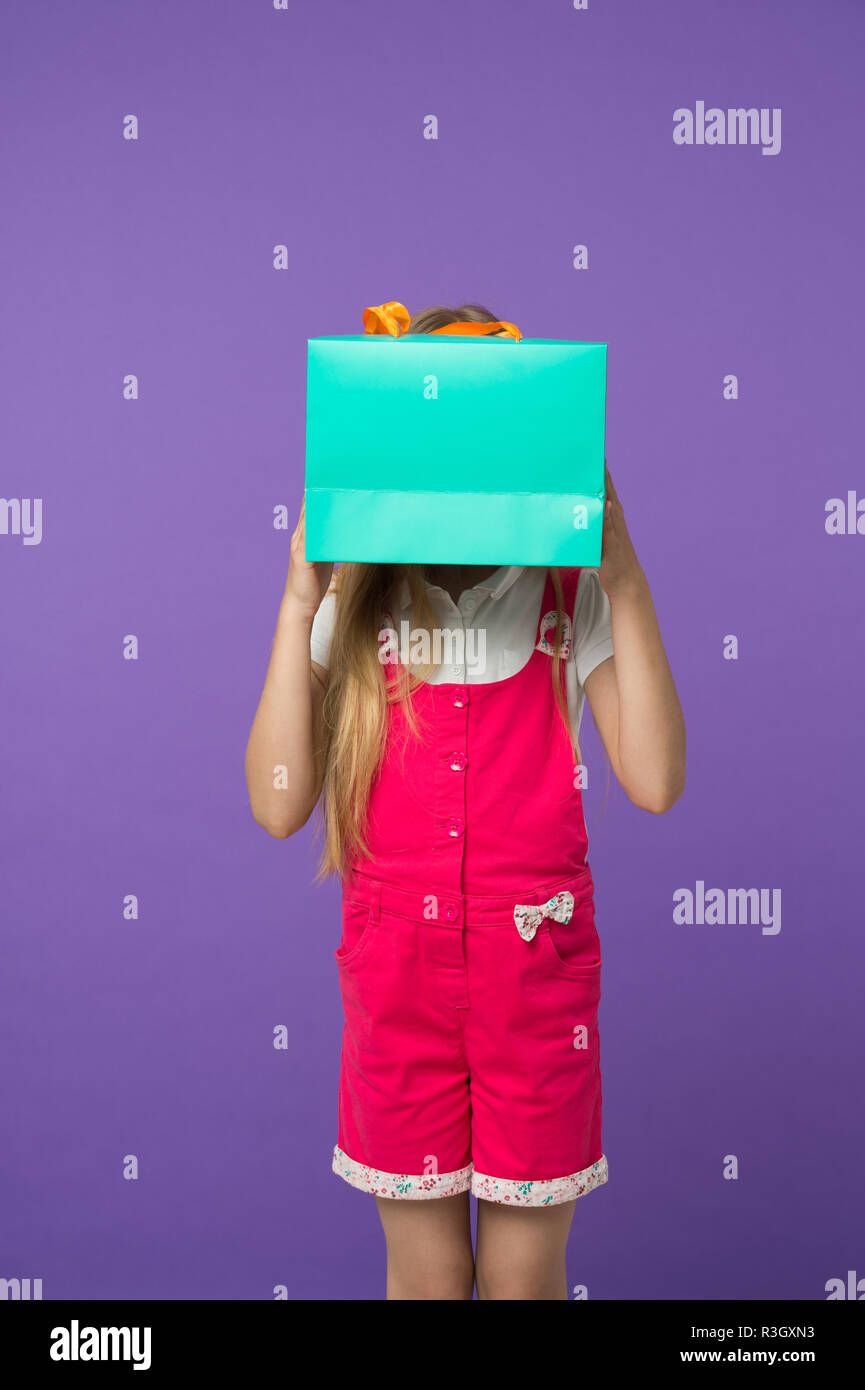 Blind of shopping. Kid holds package in front of face. Simple reminders how to shop smart. Girl cute teenager carries shopping bag. Kid bought clothin - Stock Image