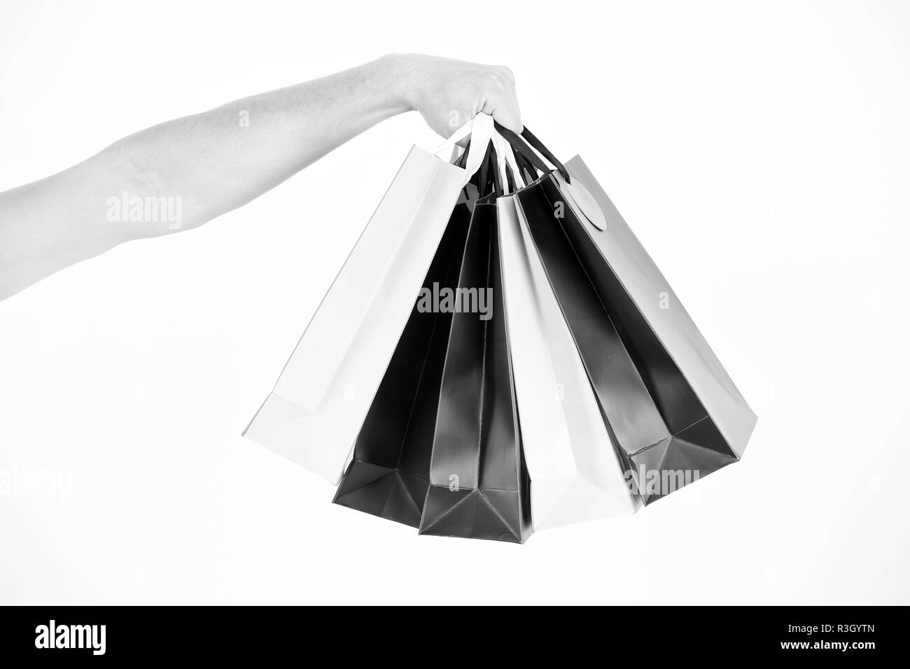 Male hand holds five shopping bags. Shopping concept. Hand holds bunch of colorful shopping bags. Shopping on black friday. Client bought lot items wi - Stock Image