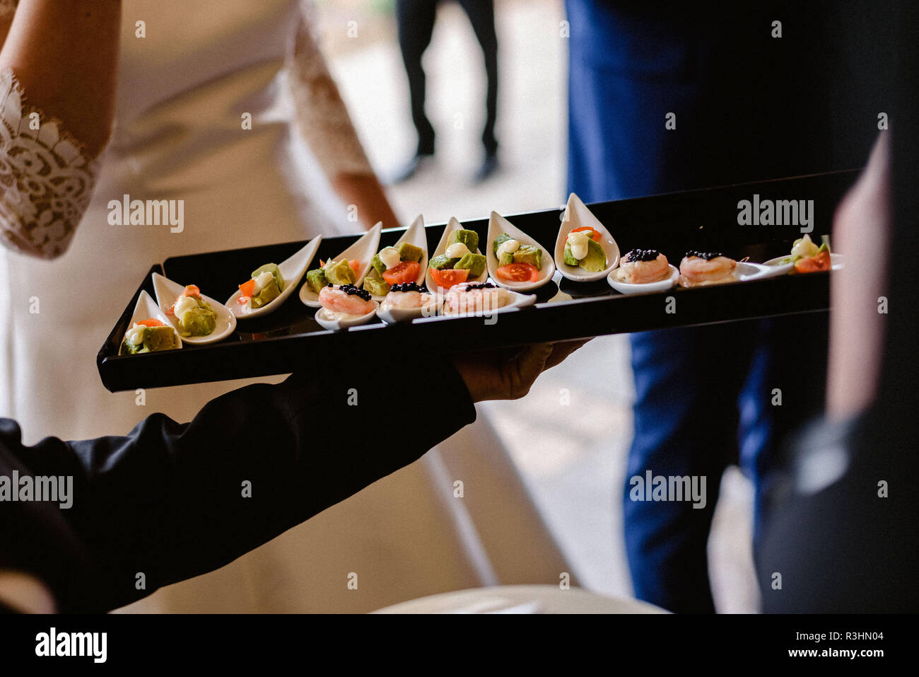 Tasty wedding appetizers served by waiters to the guests - Stock Image