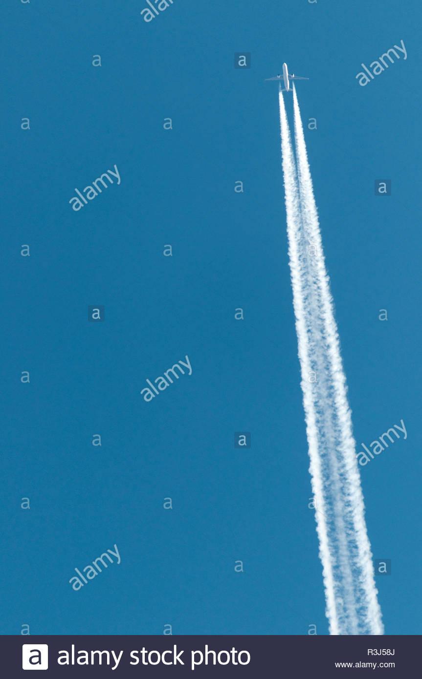 Flugzeug mit Kondensstreifen am Himmel - Stock Image