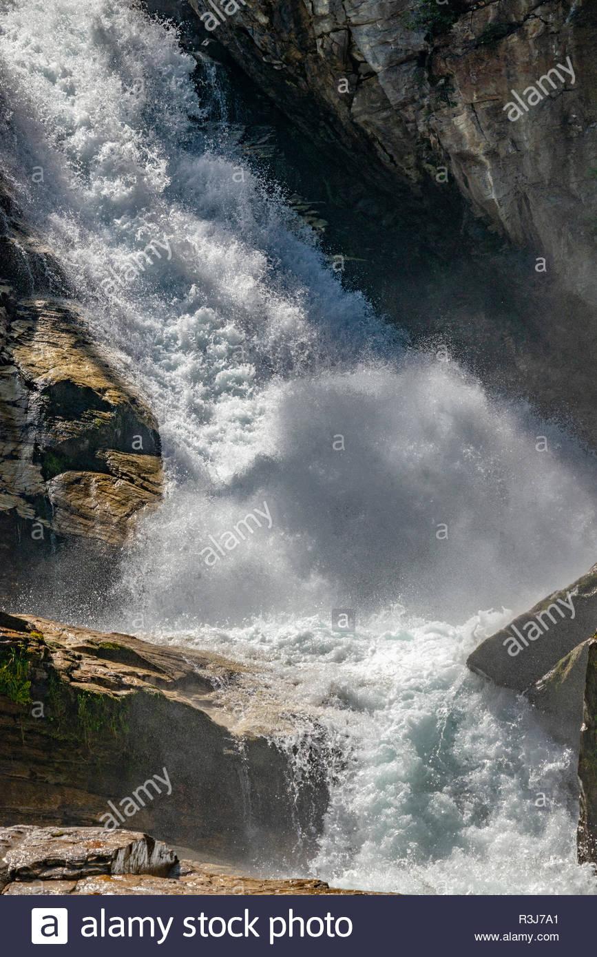 Weißende schäumende Wassermaßen stürzen mit hoher Geschwindigkeit über scharfkantige Felsen einen Wasserfall hinab - Stock Image