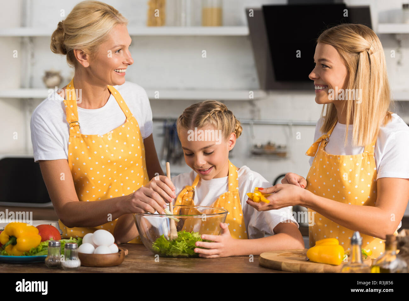 happy three generation family cooking vegetable salad together - Stock Image