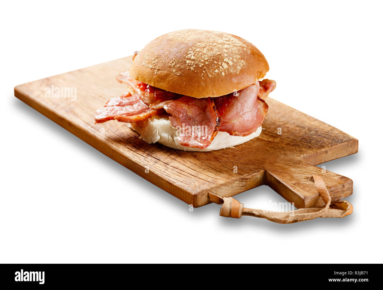 Isolated image of a bacon roll on a wooden board, with tomato sause. - Stock Image