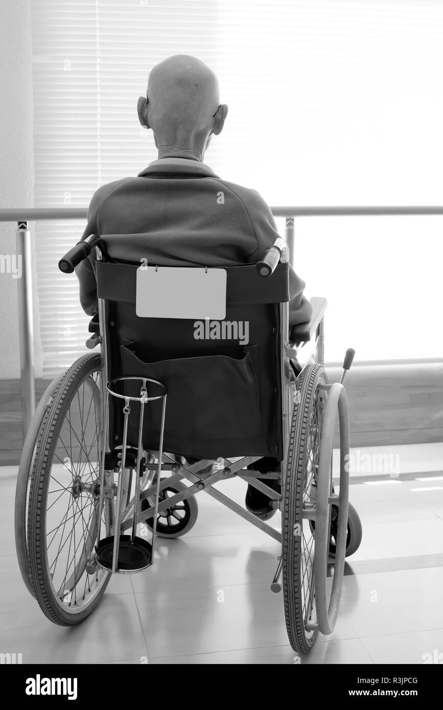 Back view of senior man in wheelchair at hospital hallway - Stock Image