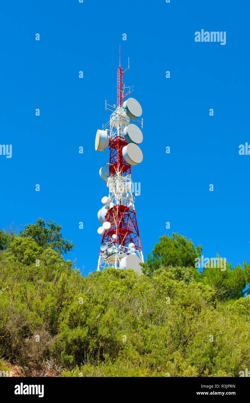 Telecommunications repeater at the head of a mountain with blue sky background - Stock Image