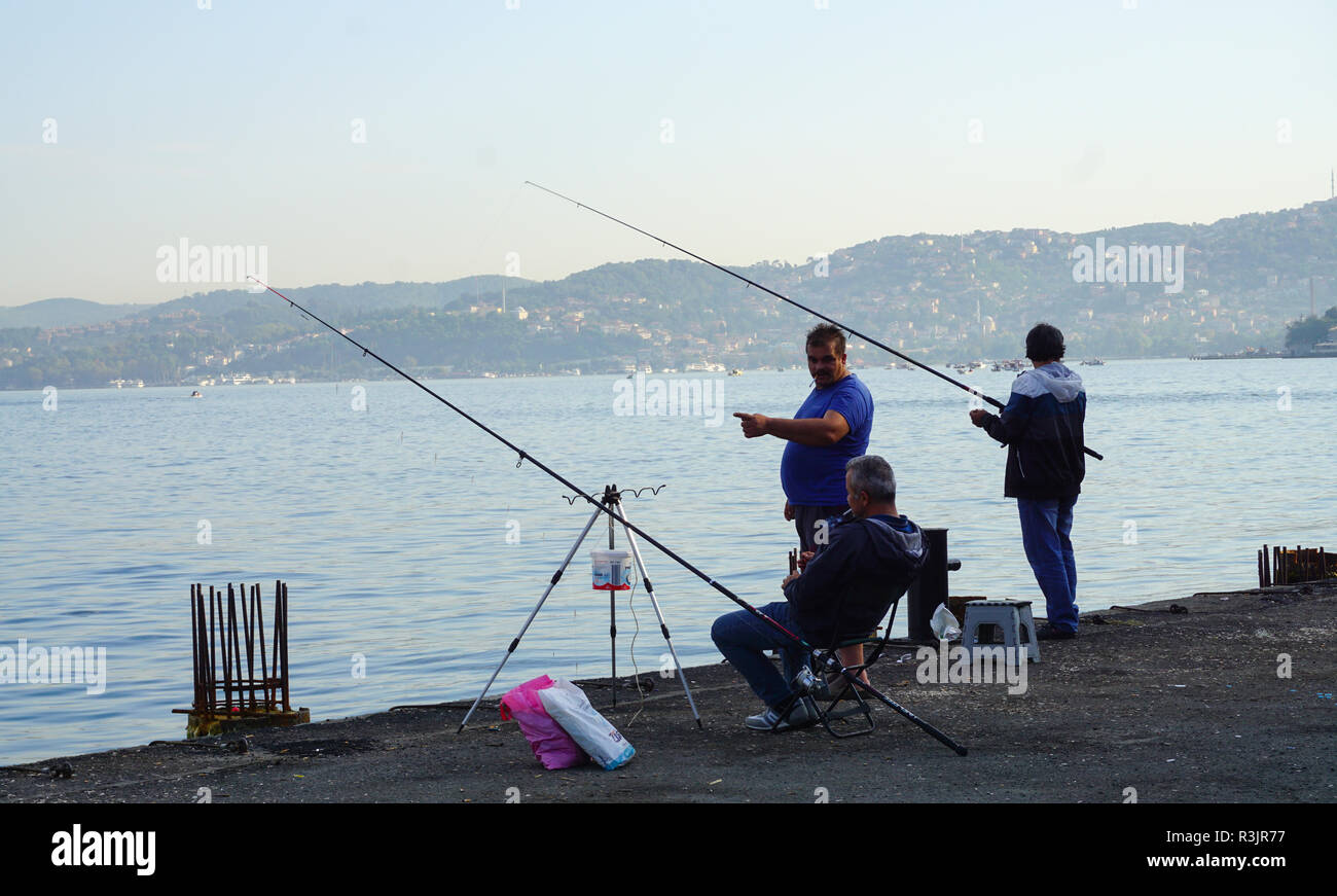 Group of fishermans relaxing at the seaside while they are trying to catch some fish. Istanbul,Turkey. Stock Photo