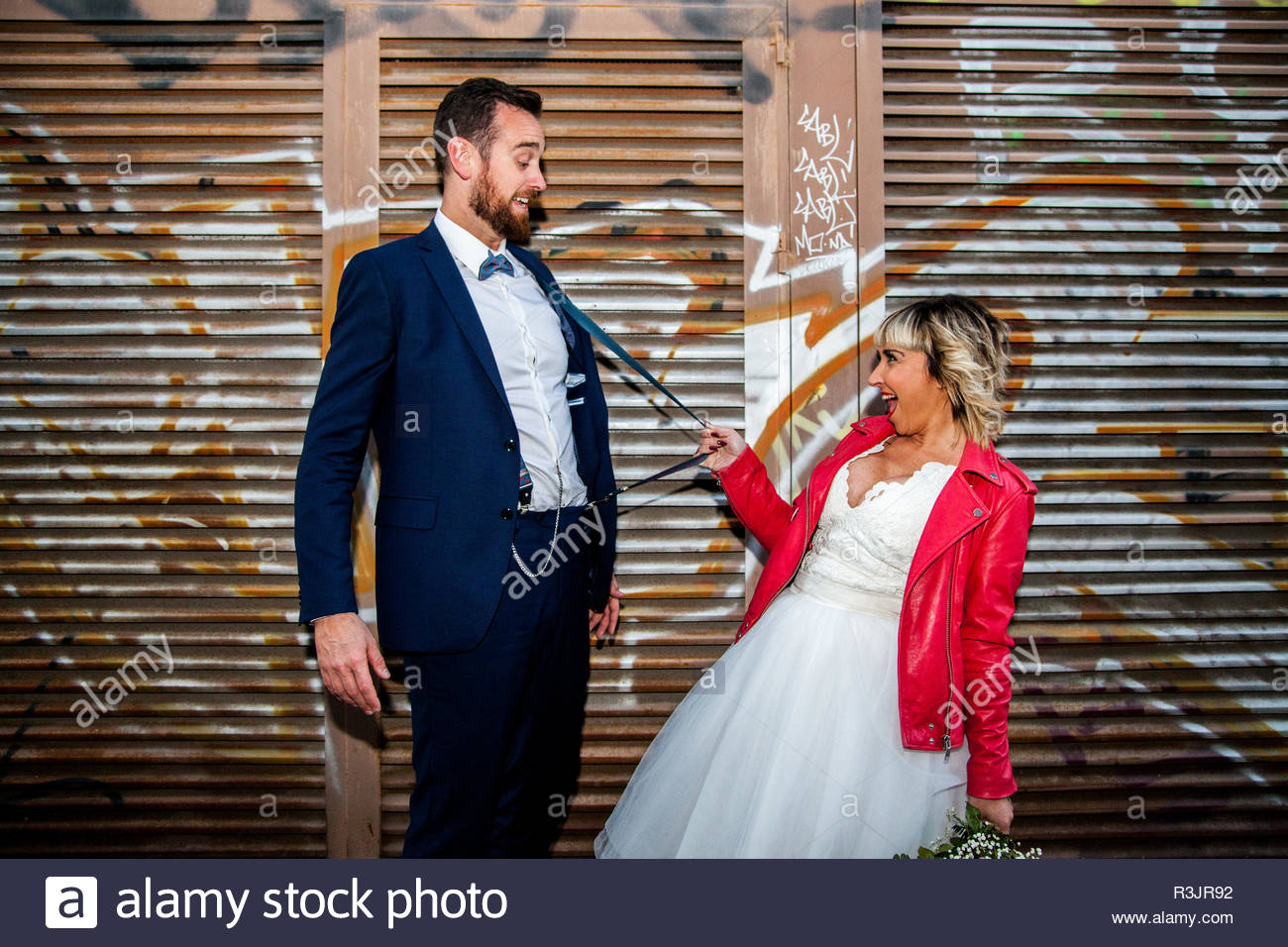 Couple of newlyweds play with suspenders in front of a graffiti metal fence. - Stock Image