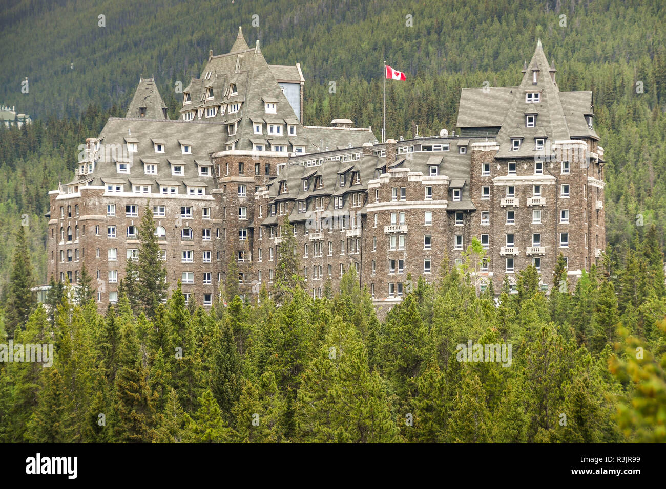 BANFF, AB, CANADA - JUNE 2018: Scenic view of the Banff Springs Fairmont Hotel surrounded by evergreen trees. - Stock Image