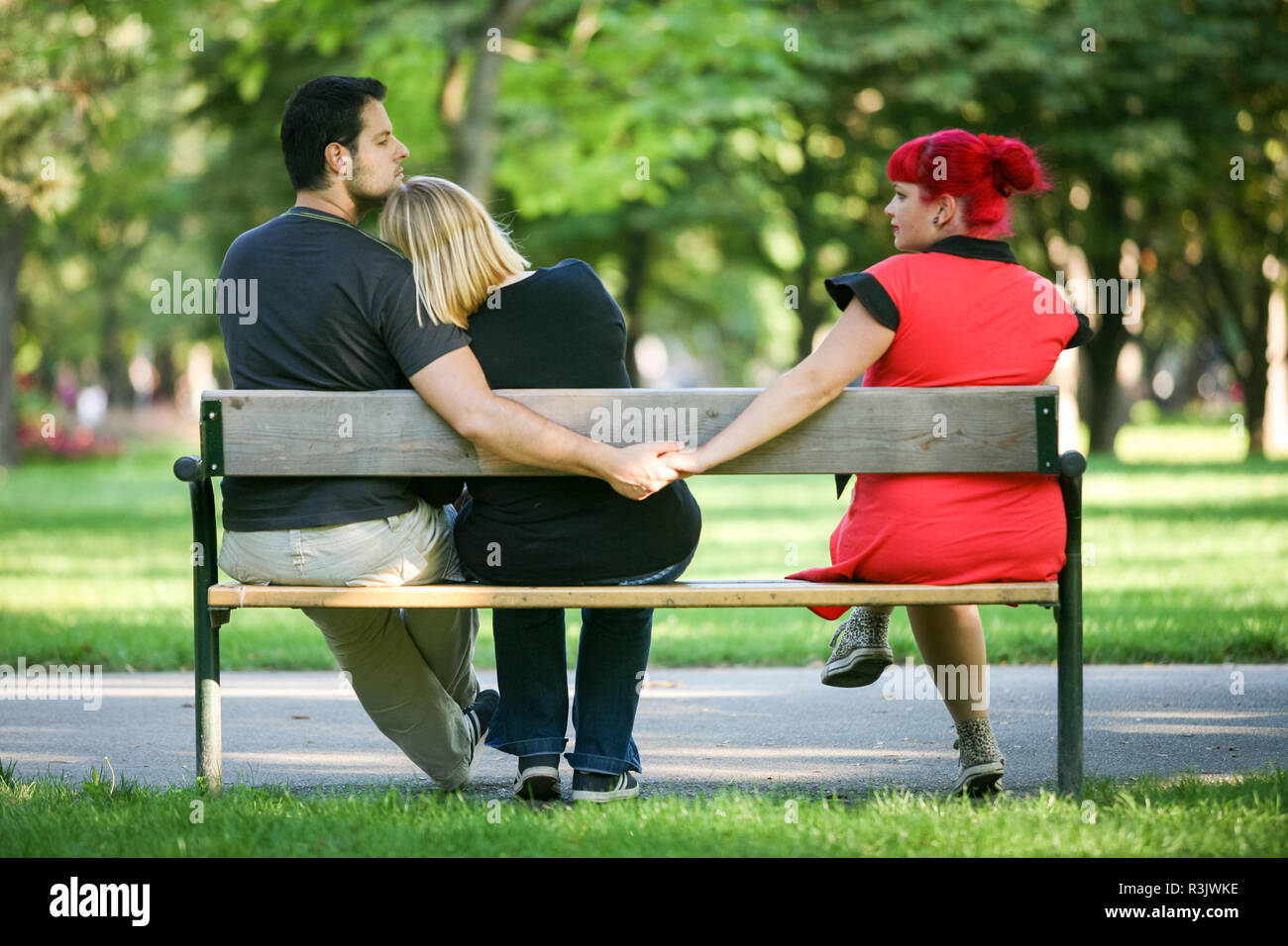 In the middle. Unfaithfulness love affair triangle. - Stock Image