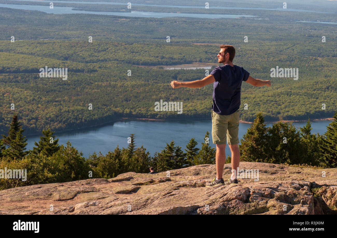 Acadia National Park, Maine--September 21, 2016. A man stands with arms outstretched looking over the scenery from a peak of Cadillac Mountain in Main - Stock Image